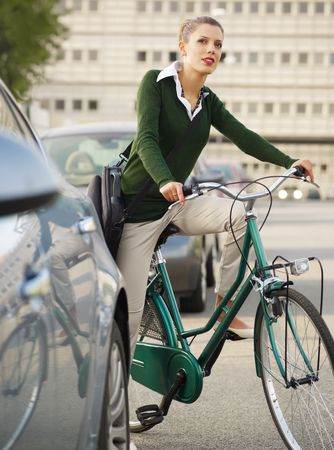 commuting: woman commuting on bicycle and looking away