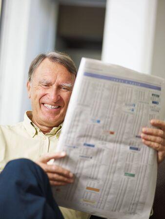 listings: Senior man reading stock listings and smiling
