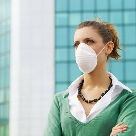 dust mask: woman standing against office building and wearing protective mask. Copy space Stock Photo