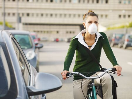 dust mask: woman with dust mask commuting on bicycle