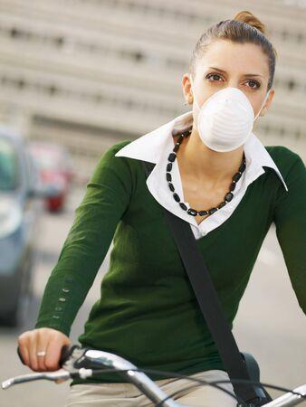 contaminacion ambiental: mujer con polvo m�scara desplazamientos en bicicleta Foto de archivo