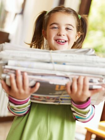 everyday scenes: girl carrying newspapers for recycling, looking at camera Stock Photo