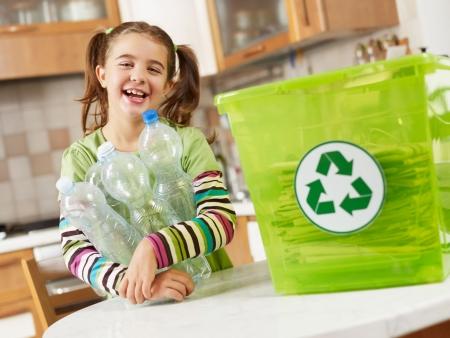 Chica mirando a cámara y la celebración de botellas de plástico para su reciclaje