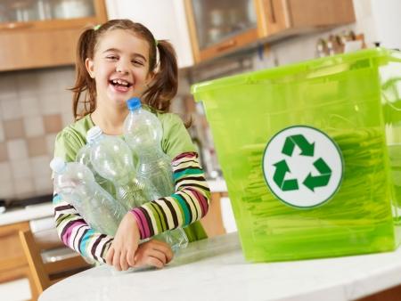 papelera de reciclaje: Chica mirando a c�mara y la celebraci�n de botellas de pl�stico para su reciclaje