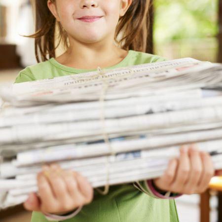 everyday scenes: ragazza che trasportano i giornali per il riciclaggio, looking at camera