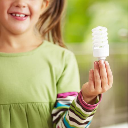 environmental responsibilities: Girl holding light bulb and smiling. Selective focus Stock Photo