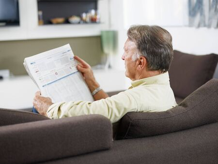 senior man sitting on sofa and reading newspaper  photo