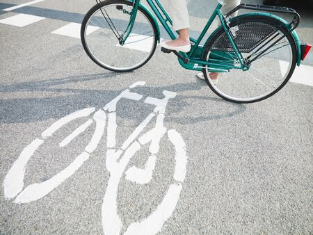 road marking: cropped view of woman commuting on bicycle. Copy space