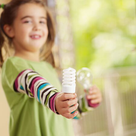 Girl holding light bulb and smiling. Selective focus, copy space Stock Photo - 5754416