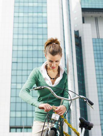 locking: female commuter locking padlock to her bike. Copy space Stock Photo
