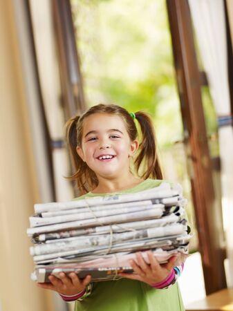 recycler: fille des journaux comptables pour le recyclage, regardant de cam�ra, copiez espace
