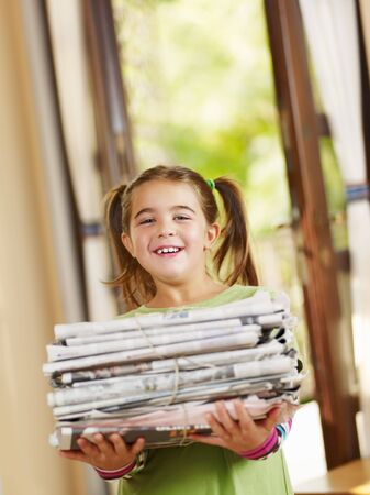 pile reuse: girl carrying newspapers for recycling, looking at camera, copy space Stock Photo