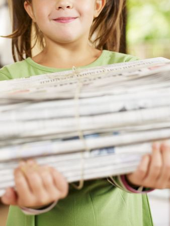 everyday scenes: girl carrying newspapers for recycling, cropped view