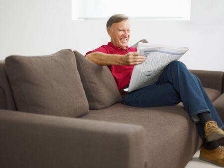 everyday scenes: legge il giornale L'anziano uomo a casa e sorridente