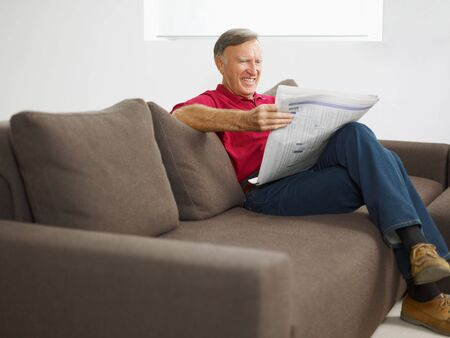 senior man reading newspaper at home and smiling photo