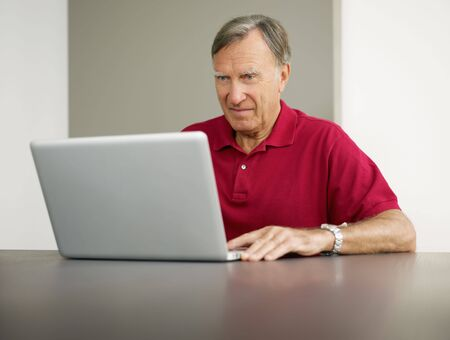 Senior man using laptop computer at home. Copy space photo