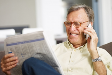 investors: Senior man reading stock listings and talking on mobile phone. Copy space Stock Photo