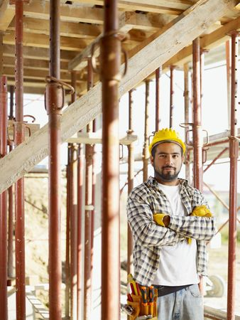 Portrait of latin american construction worker looking at camera with arms folded photo