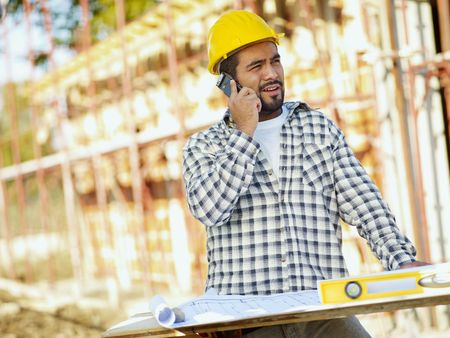 construction worker: latin american construction worker talking on mobile phone. Copy space