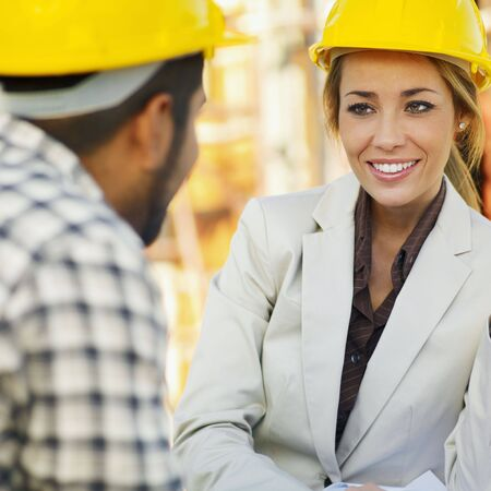 latin american construction worker and female architect talking. photo