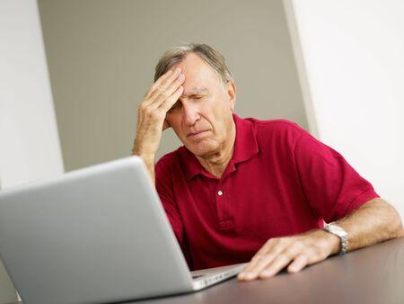 preoccupation: Senior man having headache while using laptop. Copy space