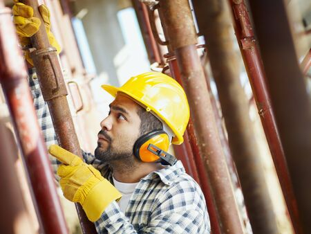 latin american construction worker fastening girder. Side view photo