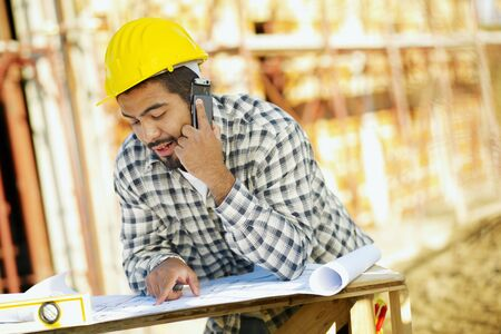latin american construction worker talking on mobile phone. Copy space photo