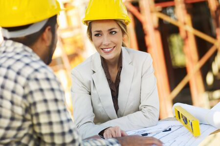 architect plans: latin american construction worker and female architect talking. Copy space Stock Photo