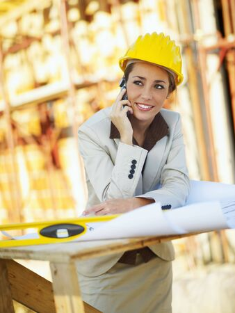 female architect talking on mobile phone in construction site Stock Photo - 5846276