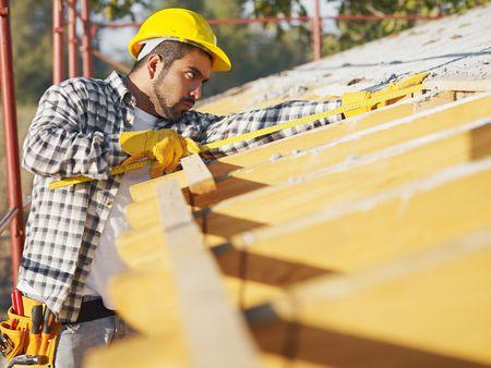 toiture maison: latino-am�ricaine des travailleurs de la construction sur le toit de maison avec un ruban � mesurer. L'espace de copie