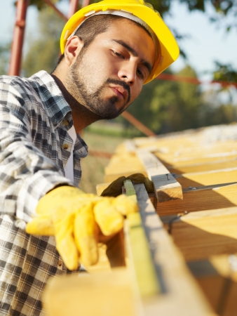 hispanic americans: latin american construction worker on house roof with measuring tape.  Stock Photo