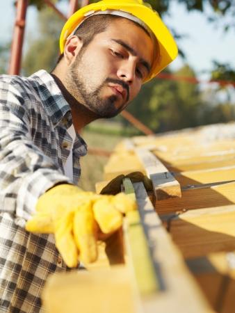 hard worker: operaio latinoamericano costruzione del tetto della casa di misura con nastro. Archivio Fotografico