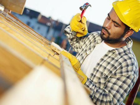 falegname: America latina operaio edile sul tetto della casa, con un martello. Copiare lo spazio