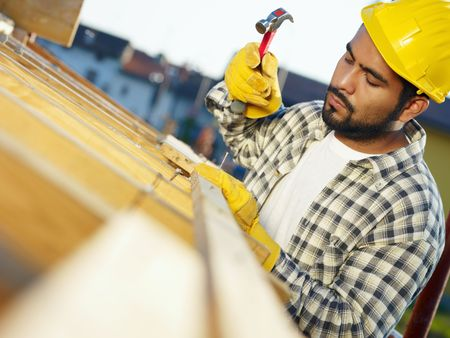 hispanic americans: latin american construction worker on house roof with hammer. Copy space Stock Photo