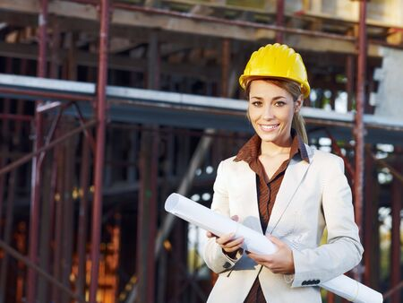 mid adult architect holding blueprints and smiling. Copy space photo