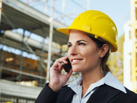 female engineer talking on mobile phone in construction site photo