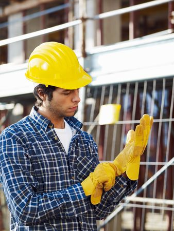 safety gloves: construction worker wearing protective gloves. Side view Stock Photo