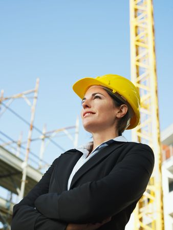 hard working woman: female engineer with arms folded looking away. Copy space