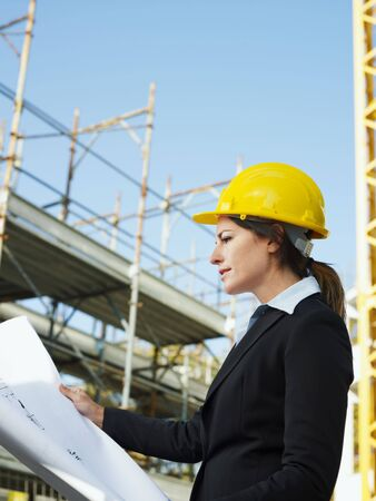 female engineer holding blueprints in construction site Stock Photo - 5928546