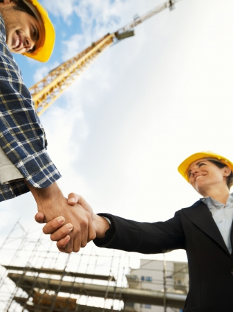female architect and construction worker shaking hands. Low angle view, copy space