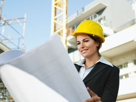 female engineer looking at blueprints in construction site photo