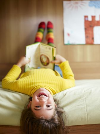 elementary kids: girl lying on bed and reading book