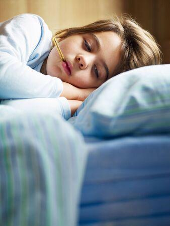 fiebre: chica tomando la temperatura en la cama. Copiar el espacio Foto de archivo