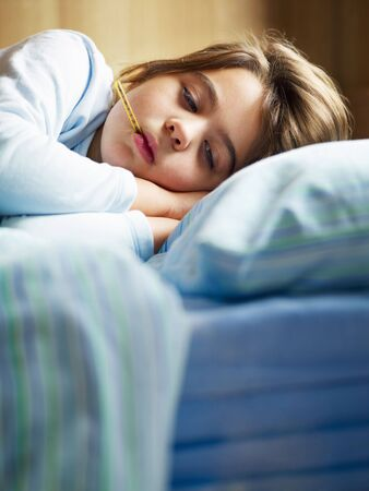sick in bed: girl taking temperature in bed. Copy space Stock Photo