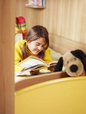 everyday scenes: ragazza sdraiata sul letto e letto il libro. Copiare lo spazio