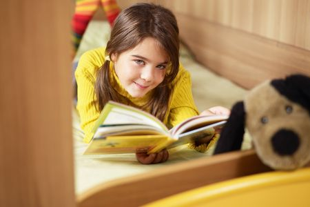 kids reading book: girl lying on bed and reading book