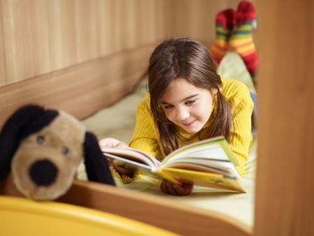 girl lying on bed and reading book. Copy space photo