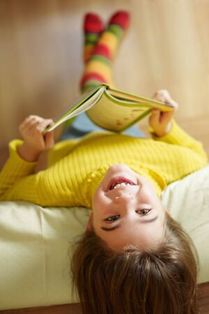 kid reading: girl lying on bed and reading book