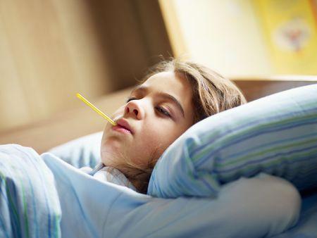 enfant malade: temp�rature de fille prise dans son lit. Espace de la copie