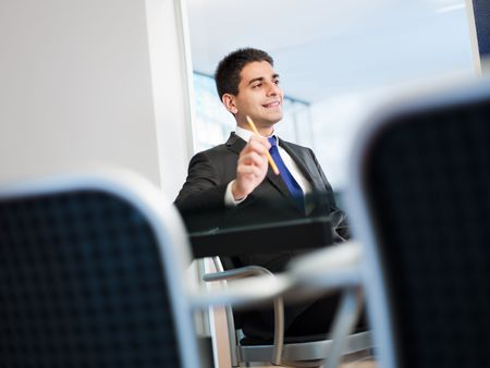 man side view: young businessman in meeting room. Copy space